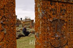 An old lady between the Khachkars in Noratus cemetery, Armenia.