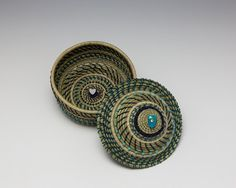 Two Hearts is a pine needle basket woven with beautiful sage pine needles and has a turquoise heart shaped stone on the lid.