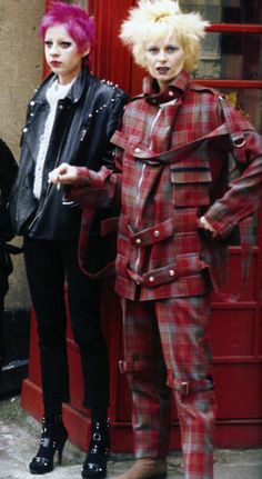 Vivienne Westwood dressed in a typical 70s punk outfit including tartan and straps with her friend in leather and studs.