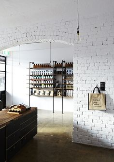 WHITE BRICK Exposed brick wall painted white, concrete floor, aged wood and industrial minimal shelves and table. Retail Interior, Cafe Interior, Interior And Exterior, White Brick Walls, Exposed Brick Walls, White Bricks, Black Brick, Deco Restaurant, Restaurant Design