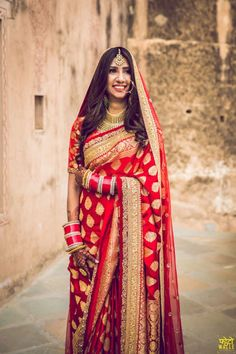 Love this Red gold bridal saree There are different rumors about the real history of the marriage dress; Nath Bridal, Bridal Sari, Indian Bridal Sarees, Designer Bridal Lehenga, Indian Bridal Outfits, Indian Bridal Fashion, Indian Bridal Wear, Wedding Sarees, Wedding Dresses
