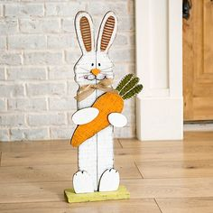 This Easter Bunny with Carrot Statue will make an adorable addition to your Easter decor. It will delight children with its sweet smile and oversized carrot.             Statue measures 9.5L x 3.5W x 29.5H in.          Crafted of wood and metal          Features an Easter bunny holding a carrot          Accented with corrugated metal and moss          Stands on its own          Hues of white, brown, orange, silver, yellow, pink, and green          Safe for covered outdoor use          Care: Dust Easter Crafts, Easter Decor, Easter Ideas, Wooden Rabbit, Cool Art Projects, Fall Deco, Seasonal Decor, Easter Bunny, Wood Crafts