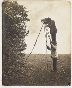 A photograph showing Cherry Kearton standing on his brother Richard's shoulders to take a picture of a bird's nest, 1900.