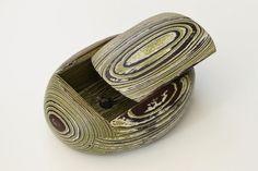 #Schatulle OVA grün  Holzschatulle mit Schiebedeckel. Eine ovale Außenhülle verbirgt einen rechteckigen Innenraum. Ein griffloser  Deckel fügt sich durch schräge Auflageflächen in seine vorbestimmte Position und kann zum Öffnen der Schatulle, durch leichtes Schieben in Längsrichtung bewegt werden. Fichtenholz mit einer speziellen Oberflächentechnik bearbeitet und farblich behandelt, ist der Werkstoff  für die schlichte und dennoch außergewöhnliche Ästhetik.  Maße:  Länge 23,0cm; Breite…