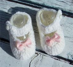 Angelic white pearl button strap crochet Booties/ pink bow, mary jane   These are made with lots of love for your little one!   Size: 0-3 Months   3-6 Months   Materials: cotton and acrylic blend yarn, thread   Always make sure keep eye on little ones as there is small objects that they can possible put in mouth, etc.   Thank you  God Bless!