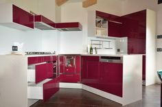 Custom lacquered kitchen with central island. This kitchen has a corian top and it's doors are in glossy finish aubergine color.