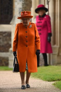 The Queen wore a bright orange jacket over a patterned green dress for the Christmas Day s...