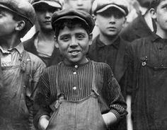Ten-year-old Secondino Libro, a child of Italian immigrants, stands at the center of a group of coworkers who all do hard industrial work in Lawrence, Massachusetts. By Lewis Hines, 1911