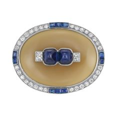 Art Deco Platinum, Agate, Sapphire and Diamond Brooch, Cartier, Paris   The oval agate panel centering 2 sugarloaf cabochon sapphires approximately 3.85 cts., flanked by 2 French-cut diamonds approximately .30 ct., edged by single-cut diamonds, spaced by 10 rectangular-cut sapphires, signed Cartier, Paris, Londres, New York, no. 0094, with French assay mark, circa 1920.