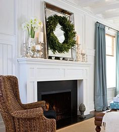 wreath on a mirror and silver candlesticks on the mantel