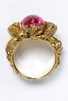 Ring, c.1880 - Gold ring with an openwork foliate bezel set with an oval quartz, artificially coloured pink, flanked by two lions resting on the shoulders of a foliated hoop.