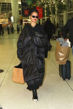 Rihanna traipses through JFK wearing an oversized, black Jessica Walsh puffer coat, oversized hoops, and Adam Selman x Le Specs sunglasses. Rihanna Mode, Moda Rihanna, Rihanna Style, Rihanna Fenty, Rihanna Outfits, Fashion Outfits, Fashion Trends, Travel Outfits, Mode Streetwear
