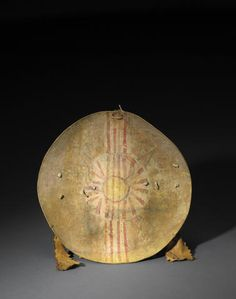 A Comanche shield and cover. Cut from thick buffalo hide, painted across the front with a vertical band of stripes and a succession of small dots crossing a sun motif in the middle, outlined rays about the perimeter, a blazing yellow center, a faint zigzag painted about the entire perimeter, black, green and red pigments also utilized, a short hide hanging strip on the reverse along with a wider carrying strap with pierced and sawtooth-edged suspensions;