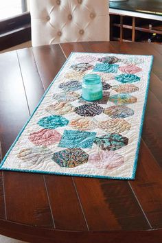 If you look closely, you can see where the name of this table quilt pattern - Square Peg Round Hole - came from. This quilt, by Wendy Sheppard, uses batiks - a great fit!
