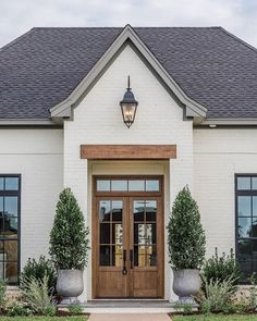 Home Exterior Ideas 'Fixer Upper' Joanna Gains Reveals New Classic Style Home, modern farmhouse exterior with white painted brick and wood front door, double front door and farmhouse exterior lights and front porch decor with planters Café Exterior, Design Exterior, Exterior Paint Colors, Exterior House Colors, Paint Colors For Home, Paint Colours, Fixer Upper Paint Colors, Fixer Upper Decor, Farmhouse Paint Colors