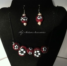 """Hand made polymer clay glossy beads. 2 oval 1 1/4"""" x 3/4 """". 3 round 3/4""""x 3/4"""". Maroon with White and Black flowers on a 20"""" black chain necklace.   Earrings are 3/4"""" x 3/4"""" round. (sane as the necklace) top and bottom of the earrings has half round pink purls. On silver hook earrings."""