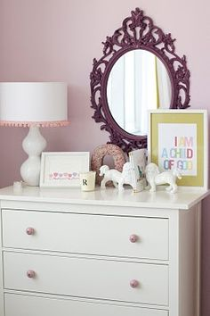 Adorable girl's nursery with pink lilac walls paint color, Ikea Hemnes 3 Drawer Chest with Zara Home pink pulls hardware, white foo dogs, white gourd lamp with white lamps shade with pink tassel trim and Ikea Ung Drill Mirror. Hemnes, Lilac Walls, Caitlin Wilson Design, Ideas Habitaciones, Ikea Nursery, Nursery Mirror, Nursery Decor, Little Girl Rooms, Girls Bedroom