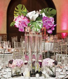 Types of Flowers: Sprigs wind up tall vases filled with purple orchids and plum mini calla lilies.