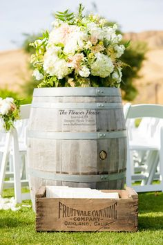 Wedding reception- Wine barrels decorated with tall white and green floral arrangement with peach and blush accents