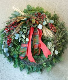 EVERGREEN WREATH DELUXE - Dress up your front door for the holidays with our fresh Evergreen Wreath Plus. It is adorned with berries, angel vine, wheat, seeded eucalyptus and a plaid and burlap bow.