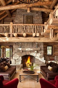 This is a very rustic room because the walls are all wood and stone which has to do with rustic. It has a very big cabin feel which also has to do with rustic. The fireplace gives comfort and the armchairs are very earth toned.