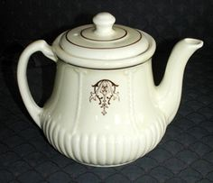 Porcelier Vitrified Yellow Ware Ribbed Tea Pot.There is a raised vertical ribbing at the base which leads your eye up to the deep brown scroll design which is flanked on either side by a raised braided cord design.