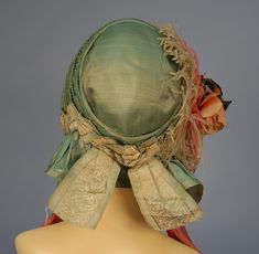 SILK DRAWN BONNET, c. 1850. Green shirred satin with narrow ribbing trimmed with green and white silk ribbon and cloth rose with pink and green feathers, wide dusty rose silk ties.