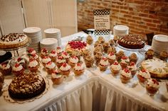 Our dessert assortment for a wedding, complete with cup cakes, mini pies and cheesecakes. Photo by Ashley Dru Photography. #historicbuilding #goshenindiana #michianawedding #weddinginspiration #weddingvenue #breadandchocolate #weddingdesserts #desserts #cupcakes #cheesecakes #minipies