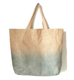"Inspired by the versatility and durability of Jute complimented with a delicate indigo ombré, this large bag is the perfect size for the city and the beach. Jute, also known as burlap is super strong and stands the test of time. Over-dyed with indigo creates a beautiful grey teal color and subtle gradation to a natural brown. Size, Large 24"" x 19"" x 6""Jute shell with cotton liningHand-dyed in Bushwick in small batchesHand wash in cool water, hang dr..."