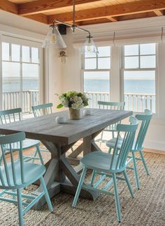 picnic-style dining table with light blue wooden chairs overlooking the ocean
