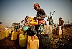 A woman fills containers from a well in Natriguel, in the drought-stricken south of Mauritania.    Photograph: Pablo Tosco/Oxfam