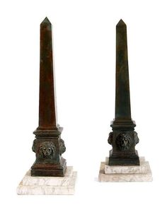 A PAIR OF LARGE BRONZE OBELISKS, LATE 19TH CENTURY, the bases set with lion masks and a stepped white marble pediment. 80cm high.