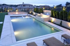 Elegant rectangle pool with white stone patio surrounded by grass on one side