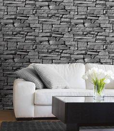 un mur en pierre de parement grise dans le salon élégant derrière le canapé blanc