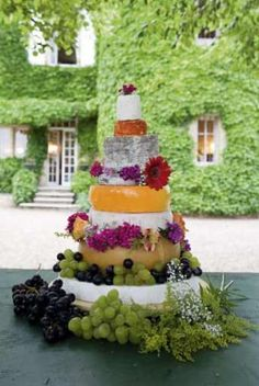 Tiers of French cheeses   decorated with grapes and flowers