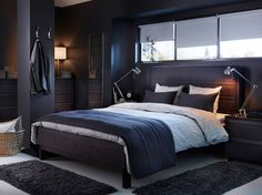 A dark grey bed with fabric headboard and bedtextiles in beige and dark grey.
