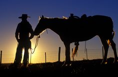 Cowboy and his Horse Silhouetted and rim lighting at sunset Ponderosa Ranch, Seneca, OR