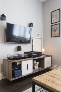 """The custom entertainment center fits the overall theme. But more importantly, it adds a decorative touch to an element that's hard to bring style to: the television. """"My advice is to not make the TV the center piece if possible,"""" says Roth. """"In Gregory's case, you can't see the TV when you walk into the space, which is great. With other clients, I have advised them to paint the wall housing the TV in a darker color so as to not accentuate it."""""""