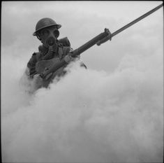 THE BRITISH ARMY IN BRITAIN, 1941. Men of the 12th Battalion, Hampshire Regiment in training at Hengistbury Head near Bournemouth, Dorset. Wearing his gas mask, a soldier advances through a smoke screen.