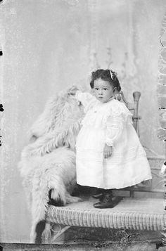Studio portrait of young girl standing on a wicker couch; circa late 19th century/early 20th century; by Norman Studios in Natchez, Mississippi