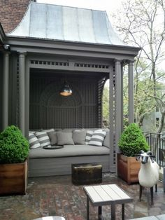 I love the lattice work on the back wall. The two containers that flank the bench appear to be boxwoods. They help to add a focal point of interest. Boxwoods are easy to maintain in containers for several years.