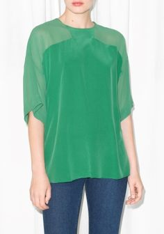 Sheer panels on the shoulders add sophisticated contrast to this luxe silk blouse with a sumptous, fluid feel.