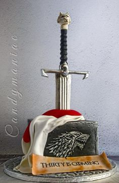 """A cake inspired from the series Game of Thrones. The sword resembles John Snow's sword and the sign is from the house of Stark. The motto is changed from """"winter is coming"""" to """"thirty is coming"""" due to the birthday boy's age. Inside the cake is. Game Of Thrones Torte, Game Of Thrones Food, Game Of Thrones Birthday Cake, Photo Cake Images, Edible Photo Cake, Sword Cake, 30th Birthday Cakes For Men, Game Of Trone, Movie Cakes"""