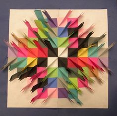 """Paper Relief Sculpture. Large white paper is cut 11"""" x 17"""". Great project to do towards the end of the school year to use up odd sizes of construction paper. Cut many colors and lots of them, 3"""" x 3"""".  Gently fold the white paper in half one way, open up,  then fold the other way, and open flat. This gives the kids an """"invisible"""" starting point. The colored 3"""" x 3"""" paper is folded in half and then at one small end, fold it towards the folded middle, like making a point on a paper airplane…"""