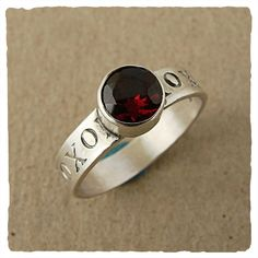 J and I Jewelry Hugs and Kisses Ring  X & O stamped sterling band with 6mm faceted garnet Handmade in USA. Whole sizes 5 to 10