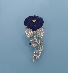 AN ART DECO LAPIS LAZULI & GEM-SET FLOWER BROOCH/PENDANT, BY KOHN   Designed as a carved lapis lazuli convulvulus to diamond and green enamel leaves, stem and bud, circa 1925, 6.0 cm long,  Signed Kohn.