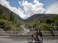 Men ride past on the Karakoram Highway at a viewpoint of the Rakaposhi Peak in the Karakoram mountain range in Pakistan