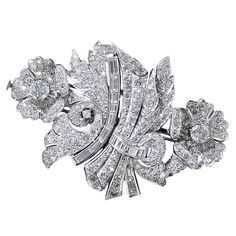 Art Deco Platinum and Diamond Floral Clips and Brooch .An extra-lovely and glittering pair of 1930s-1940s vintage clips and brooch combination masterfully rendered in a graceful asymmetrical floral design.