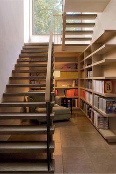 【敢えて小さく作りこみ】大きな造作本棚と一人掛けのソファのあるコンパクトな階段下のリーディングヌック