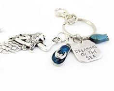 This+pretty+little+key+chain+is+beach+inspired+with+its+large+silver+tone+mermaid+charm+makes+a+perfect+gift+for+a+teacher,+teen+or+beach+lover.+ There+is+a+dreaming+of+the+sea+quote+charm+along+with+a+sea+blue+glass+fish+bead+and+a+cute+sea+flip+flop+sandal+charm.  MEASUREMENTS:+Mermaid+measu...